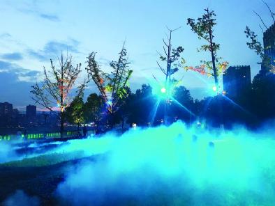 """立秋过后,华灯初上,朦胧的喷雾、斑斓的色彩、多变的图案,将夜晚的南滨路装扮成一个""""人间仙境"""",如梦似幻。"""