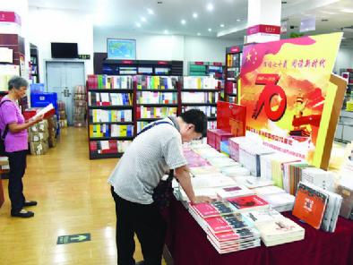 """8月9日,万州区新华书店,市民正在选购""""新中国成立70周年""""系列丛书。"""